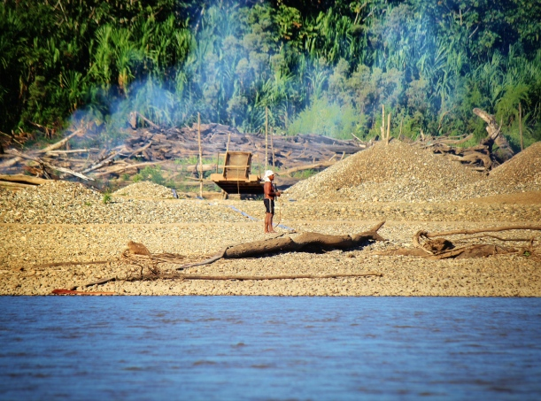 Mining standing in front of a caranchera (semi-mechanized mining equipment including motor and pump, sluice box, carpeted ramp for capturing gold flakes). During the dry season (especially July-September) it is common to see smoke along beaches, where felled trees and gathered driftwood (locally referred to as palizada) incinerated to make space for mining sites.