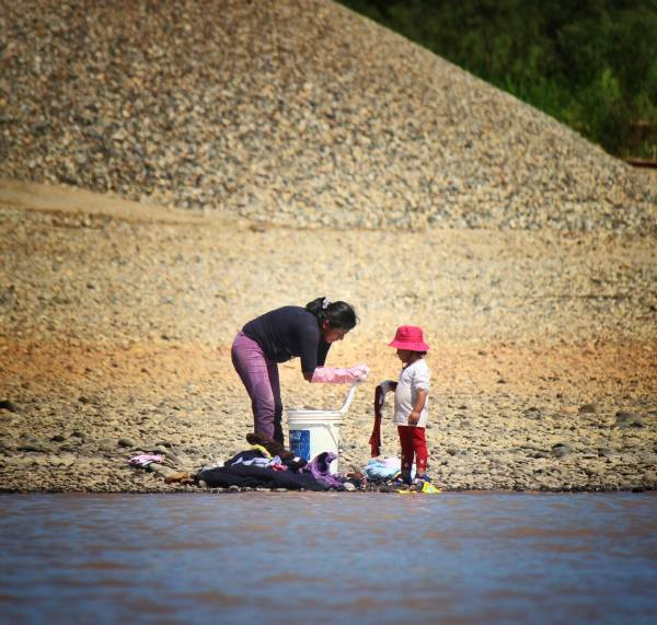A young child helps her mother wash clothes for Miners on the Madre de Dios River